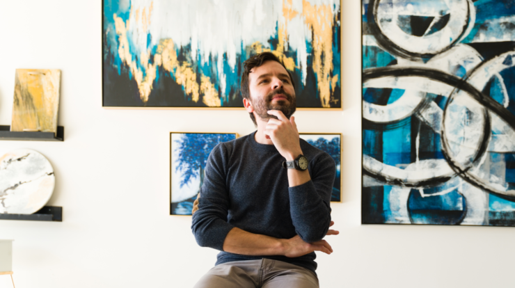 Image of a man thinking in front of paintings